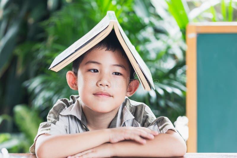 Азиатский мальчик держа книгу на голове стоковая фотография