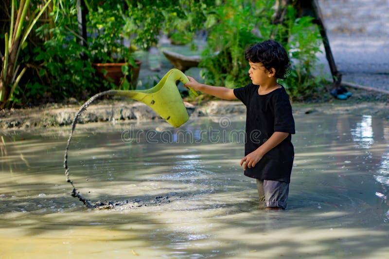 Азиатский мальчик, играющий в грязи в веселом месте в грязной яме, построенной для детей, чтобы играть вместе стоковые изображения rf