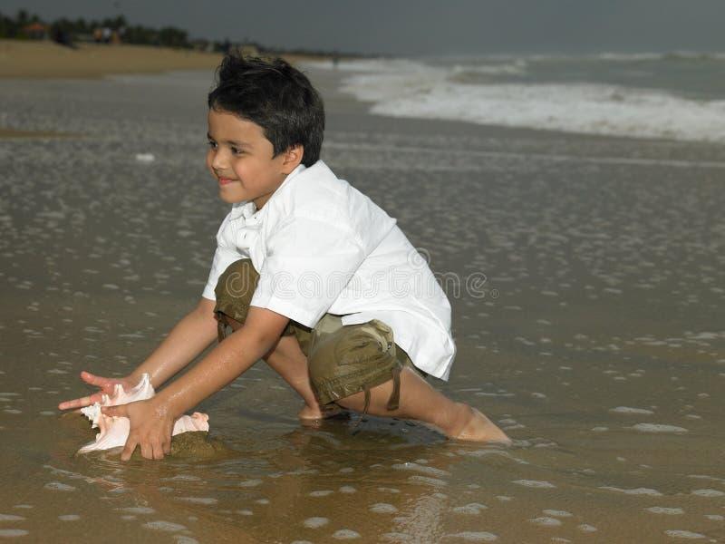 азиатский мальчик играя морскую воду стоковая фотография rf