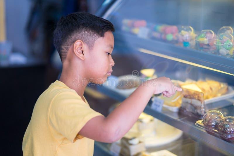 Азиатский мальчик ребенк ждать на магазине пекарни и выбирая пекарню которая он для того чтобы полюбить стоковая фотография