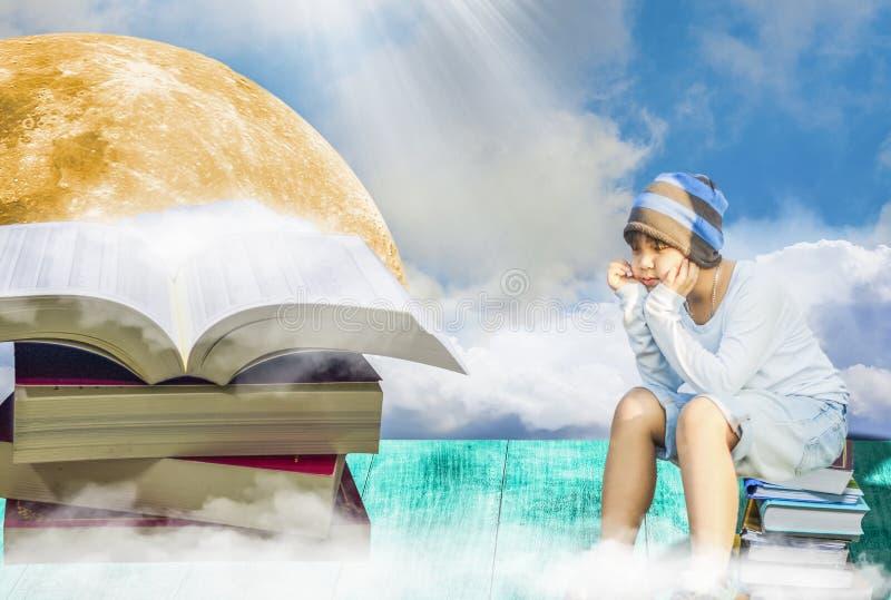Азиатский мальчик, сидя на куче книг стоковая фотография rf
