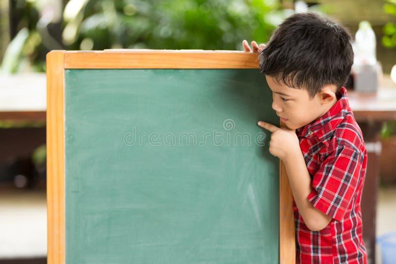 Азиатский мальчик указывает рука на классн классном стоковые изображения rf