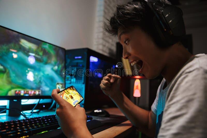 Азиатский мальчик gamer кричащий пока играющ видеоигры на smartphon стоковое фото