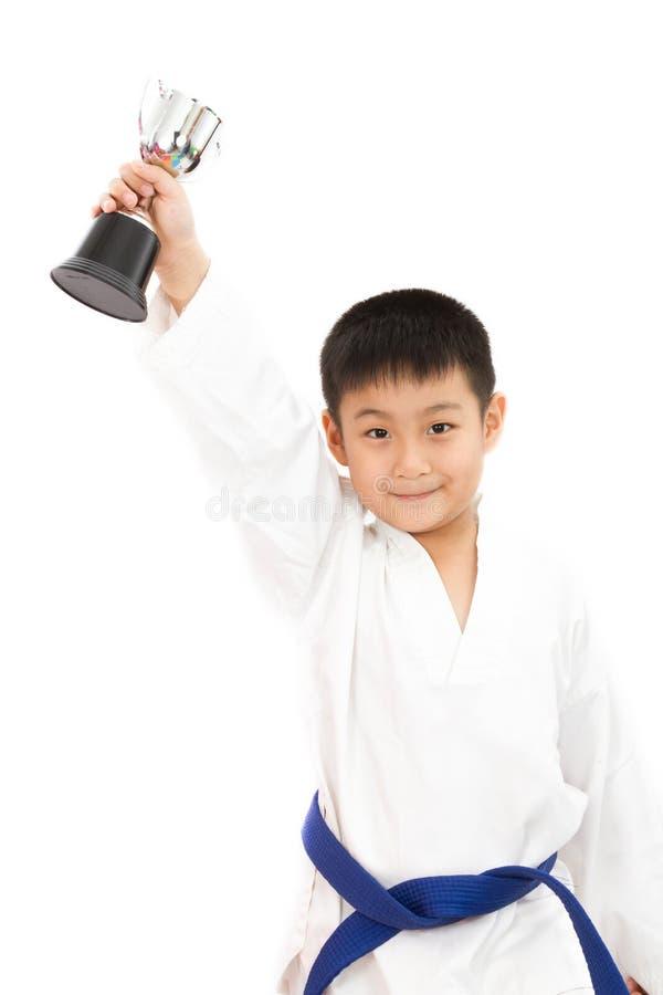 Азиатский маленький мальчик карате держа чашку в белом кимоно стоковые изображения rf