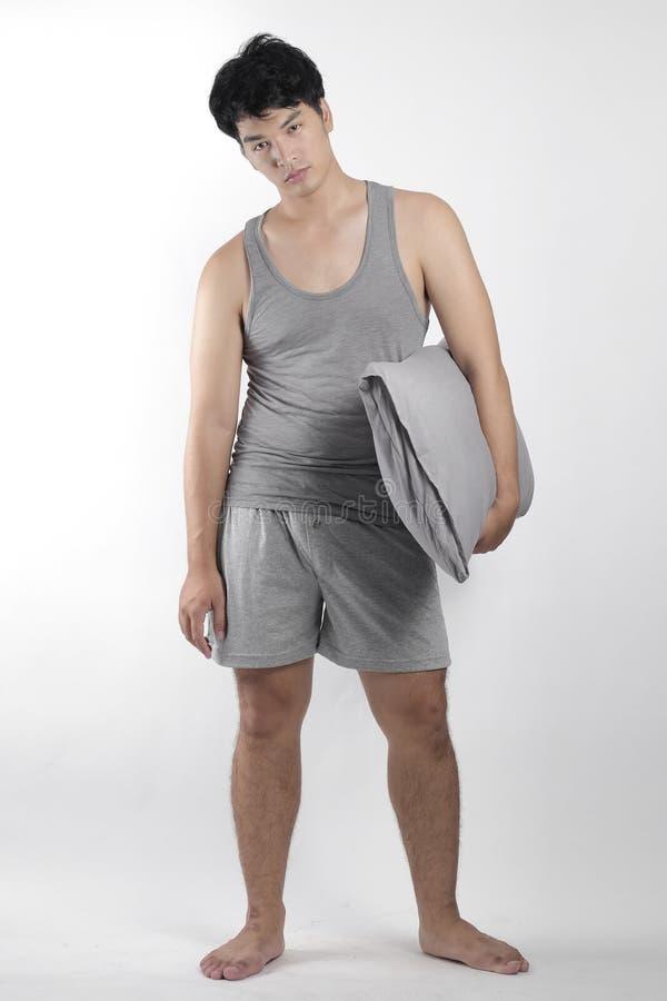 Азиатский мальчик в серых пижамах с подушкой стоковое фото