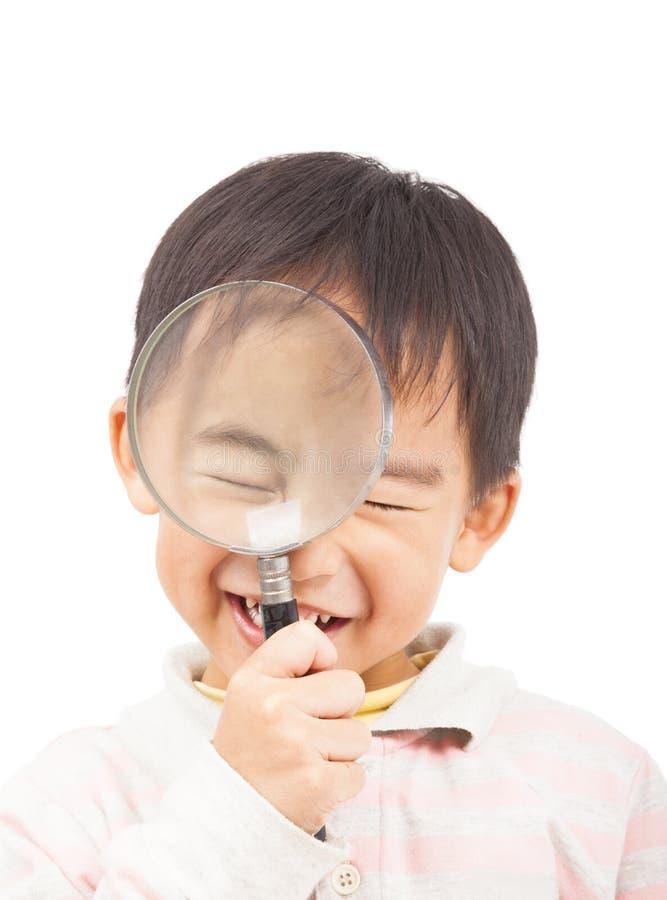 Азиатский мальчик держа глаза увеличителя и конца стоковые изображения rf
