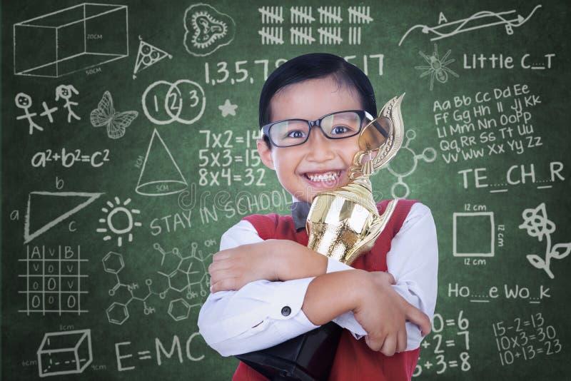 Азиатский мальчик держа трофей в классе стоковые фотографии rf