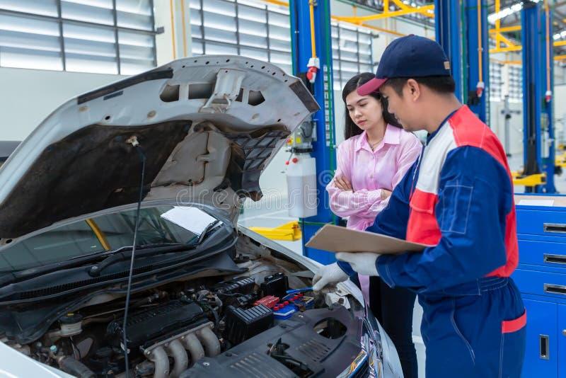 Азиатский механик автомобиля и женщина клиента говоря с механиком автомобиля в пункте обслуживания автомобиля, обоих стоят рядом  стоковые фото