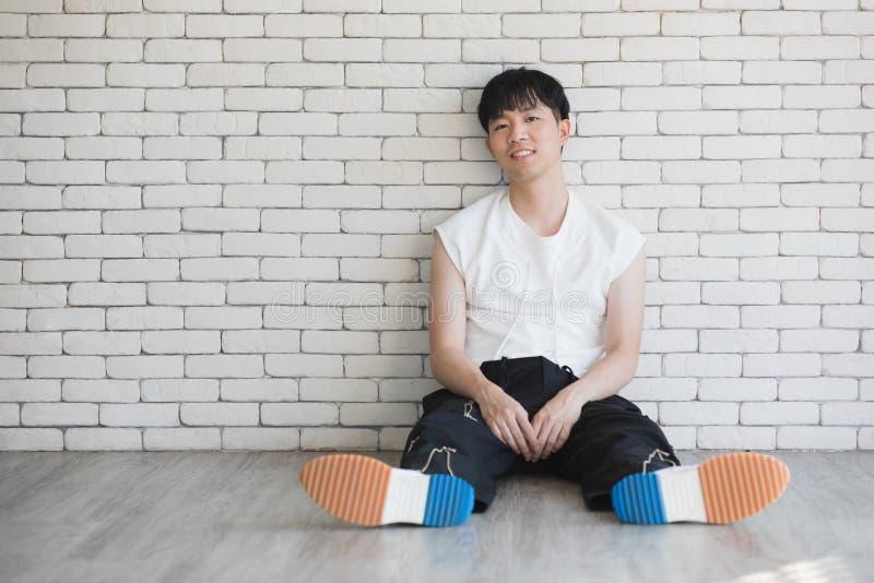 Азиатский модельный человек сидя на поле и колене вверх стоковые изображения rf