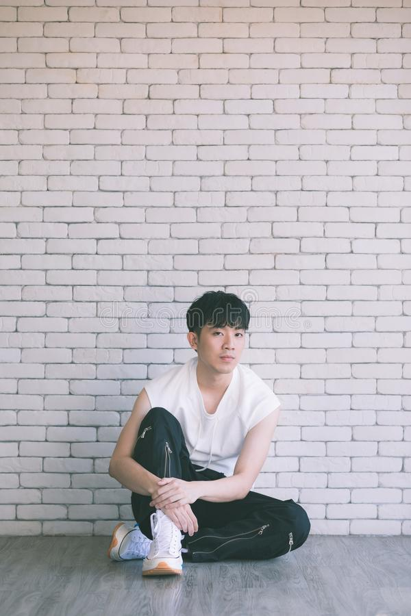 Азиатский модельный человек сидя на поле и колене вверх стоковое фото