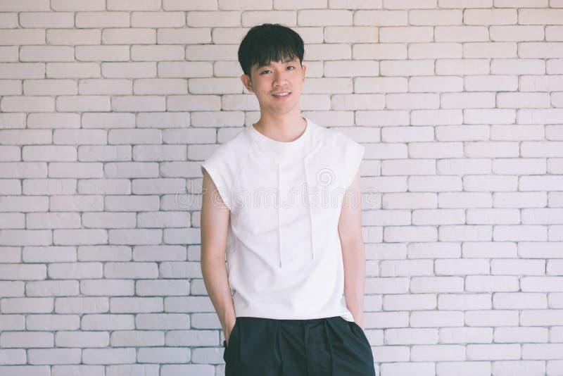 Азиатский модельный человек сидя на поле и колене вверх стоковые фото