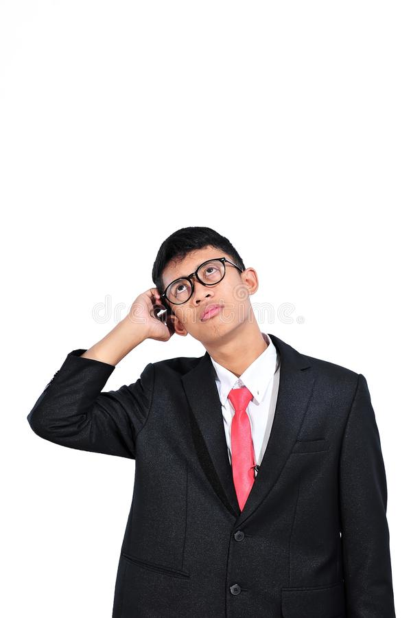 Азиатский молодой бизнесмен думая о вопросе, руке на голове, задумчивом выражении Запутанность с внимательной стороной Концепция  стоковые фото