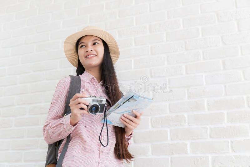 Азиатский молодой турист backpacker, молодое азиатское держащ камеру и карту в белой предпосылке стоковые фотографии rf