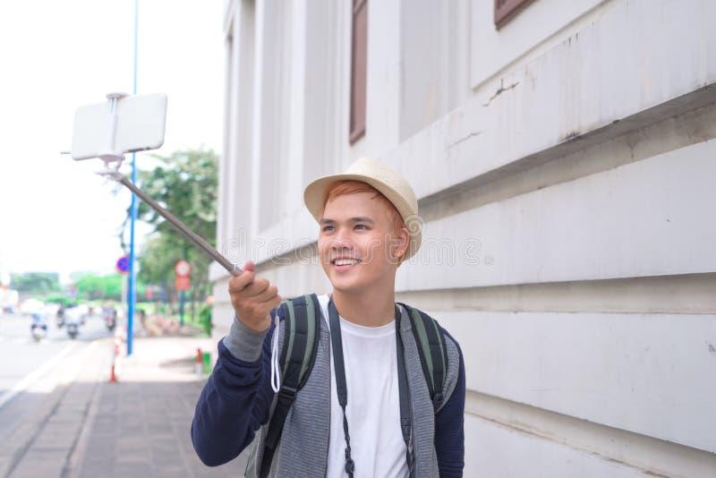 Азиатский молодой человек делая selfie с ручкой стоковое изображение