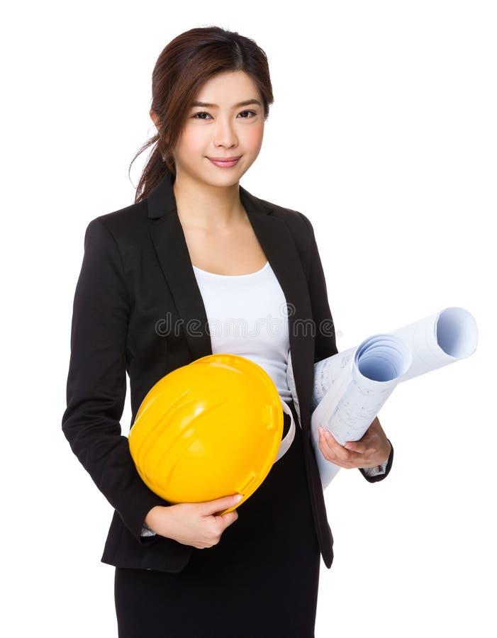 Азиатский молодой инженер с желтыми шлемом и светокопией стоковые изображения
