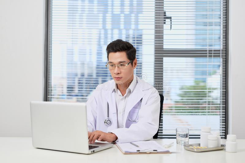Азиатский мужской доктор печатая на ноутбуке пока сидящ на стоковое фото