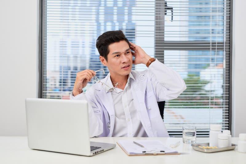 Азиатский мужской доктор печатая на ноутбуке пока сидящ на стоковые изображения rf
