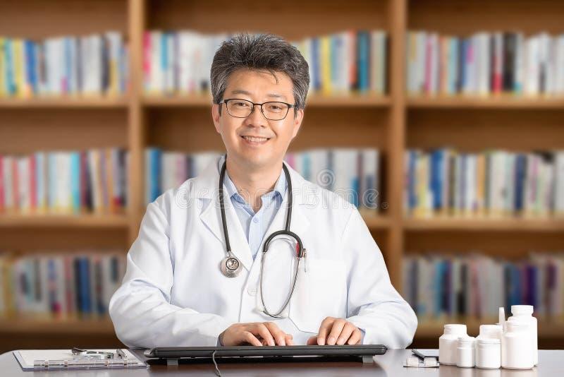 Азиатский мужской доктор сидя на усмехаться стола стоковая фотография