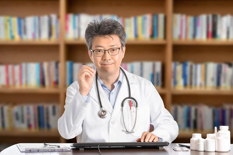 Азиатский мужской доктор сидя на усмехаться стола стоковые фото