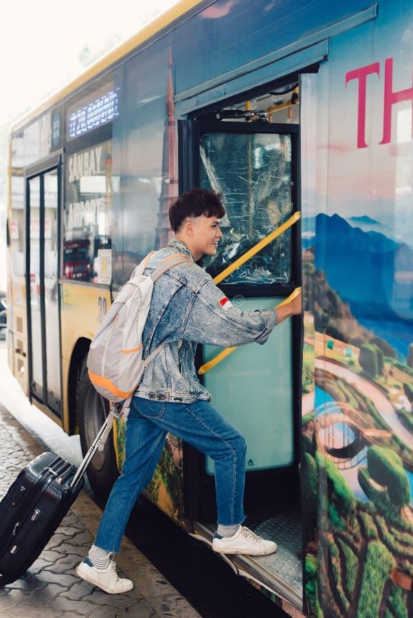 Азиатский мужской молодой путешественник получая на туристическом автобусе для перемещения стоковые фотографии rf