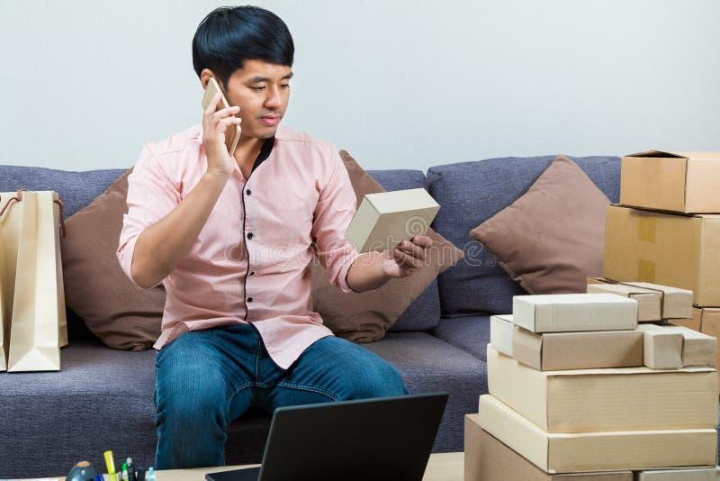 Азиатский мужской онлайн продавец говоря на телефоне с его клиентом стоковые фото