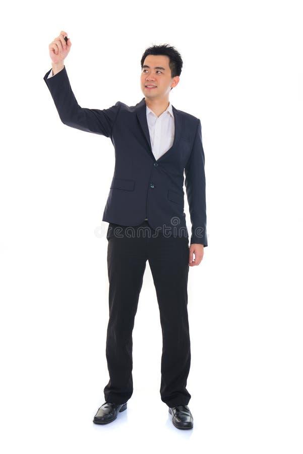 Азиатский мужчина в сочинительстве пальто что-то на стеклянной доске с отметкой стоковые изображения