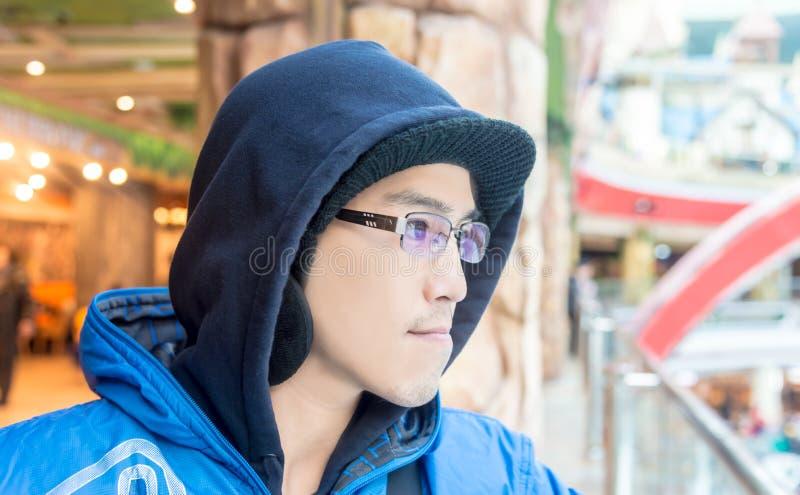 Азиатский мужчина в солнечных очках носки клобука смотря вперед самостоятельно стоковые фотографии rf