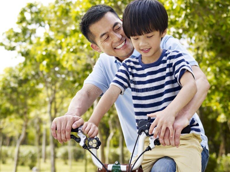 Азиатский отец и сын наслаждаясь велосипед outdoors стоковое изображение