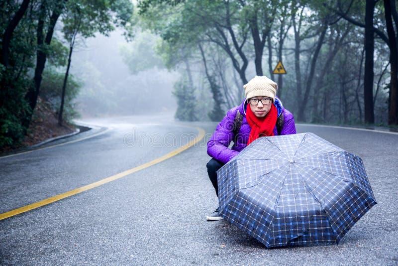 Азиатский парень на дороге с зонтиком стоковое изображение