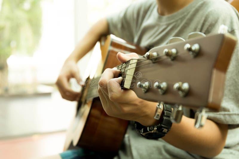 Азиатский подросток играя акустическую гитару стоковое изображение rf