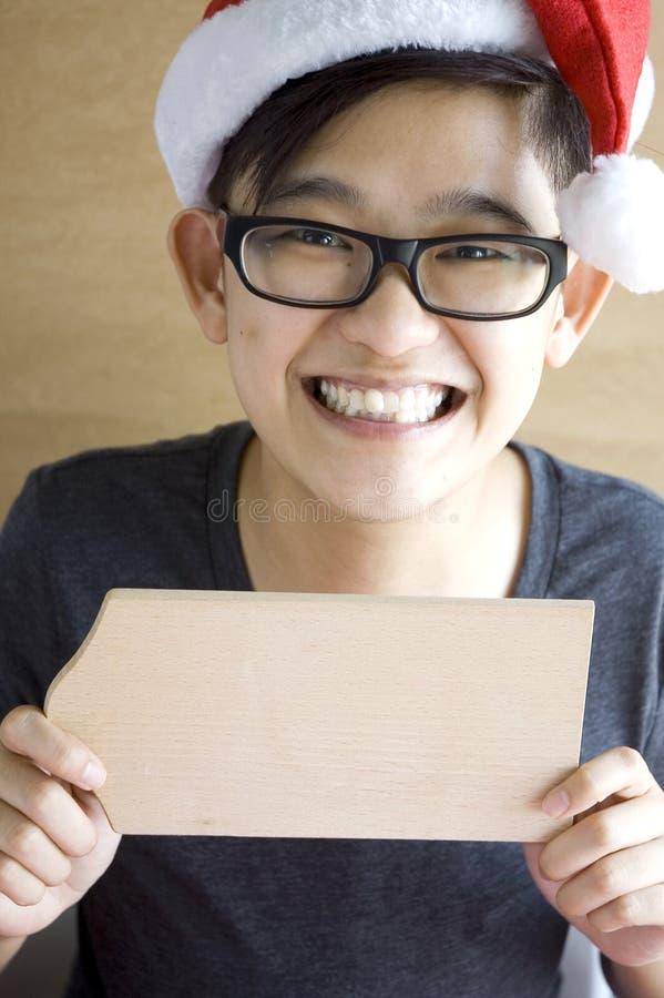 Азиатский подросток показывая пустую деревянную доску стоковые изображения