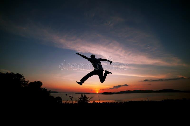 Азиатский путешественник человека скачет na górze горы тропического леса внутри стоковое фото rf