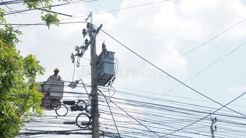 Азиатский работник для того чтобы изменить новый поляка электричества в фуникулере близко стоковое фото rf