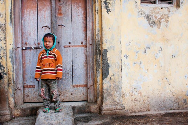 Азиатский ребенк стоя перед деревянными дверями стоковая фотография