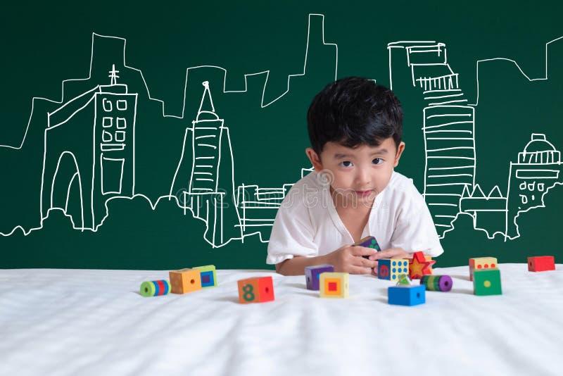 Азиатский ребенк уча путем играть с его воображением о buildin стоковые изображения rf