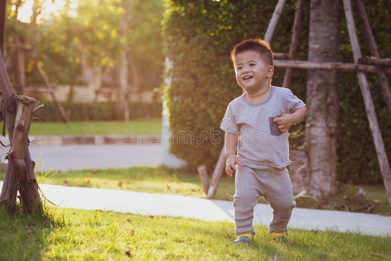 Азиатский ребенок бежать в саде во время вечера, стоковые изображения rf
