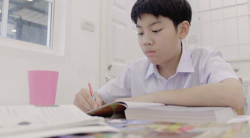 Азиатский ребенок в форме студента для того чтобы сделать домашнюю работу дома стоковое изображение rf