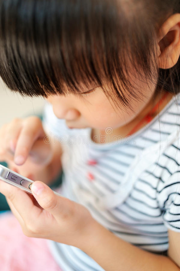 Азиатский ребенок играя телефон руки стоковые фотографии rf