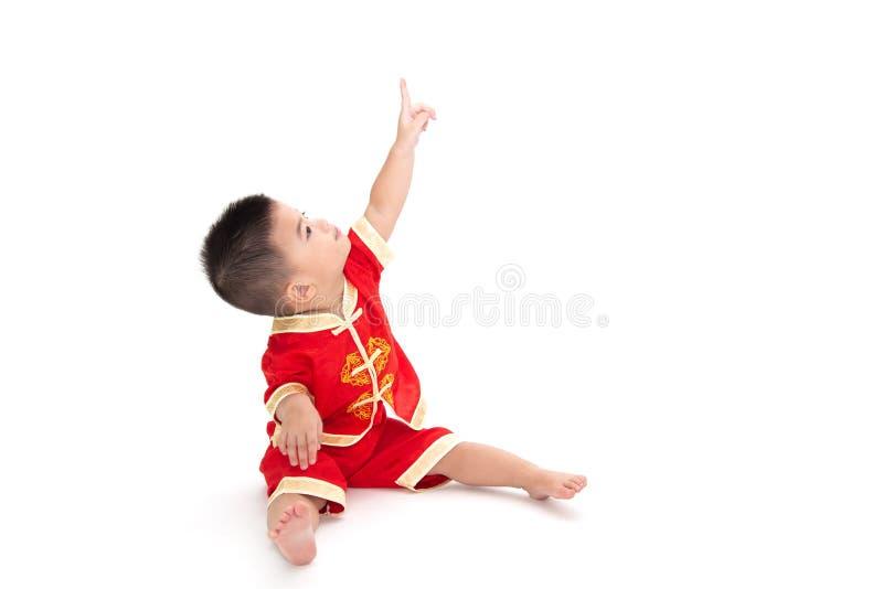 Азиатский ребенок сидит и указывающ на верхний и нося изолированный костюм традиционного китайского на белой предпосылке, стоковые изображения