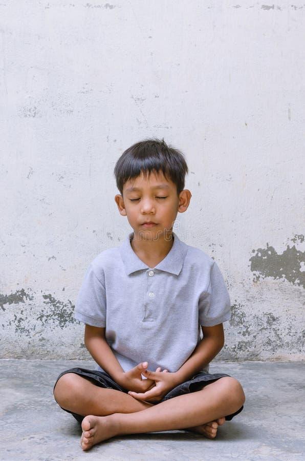 Азиатский ребенок сидя для того чтобы размышлять стоковые изображения