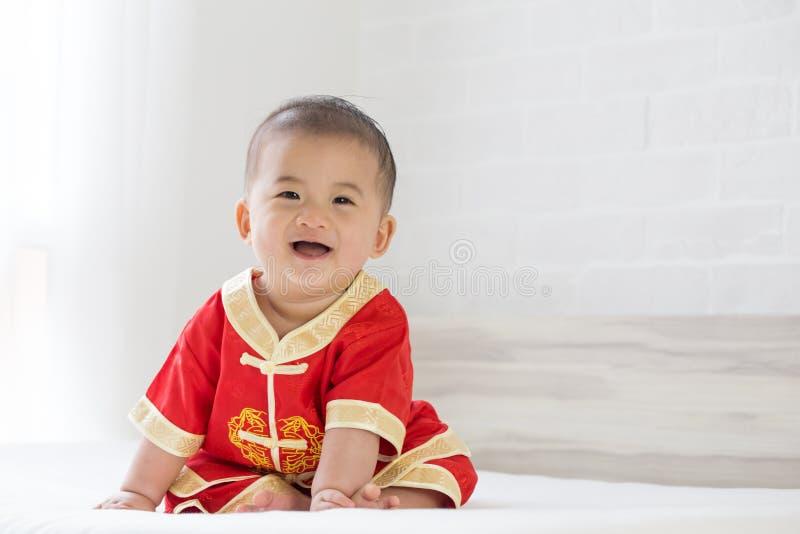 Азиатский ребенок усмехаясь с обмундированием традиционного китайского стоковые изображения rf