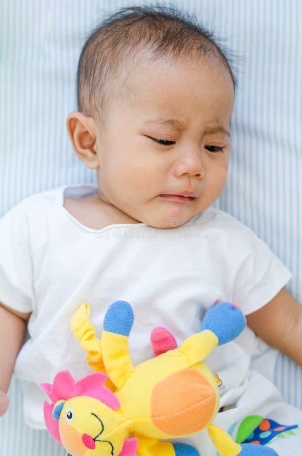 Азиатский ребёнок плача на кровати стоковые изображения rf