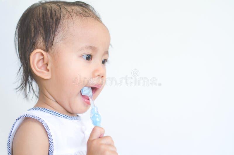 Азиатский ребёнок чистя ее зубы щеткой стоковые изображения