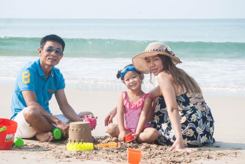 Азиатский родитель и милая дочь сделали замок песка вместе с стоковые изображения rf