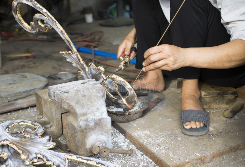 Азиатский сварщик работая на стороне улицы стоковое фото