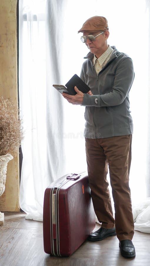 Азиатский старший бизнесмен с винтажным багажом и умным телефоном w стоковое изображение rf