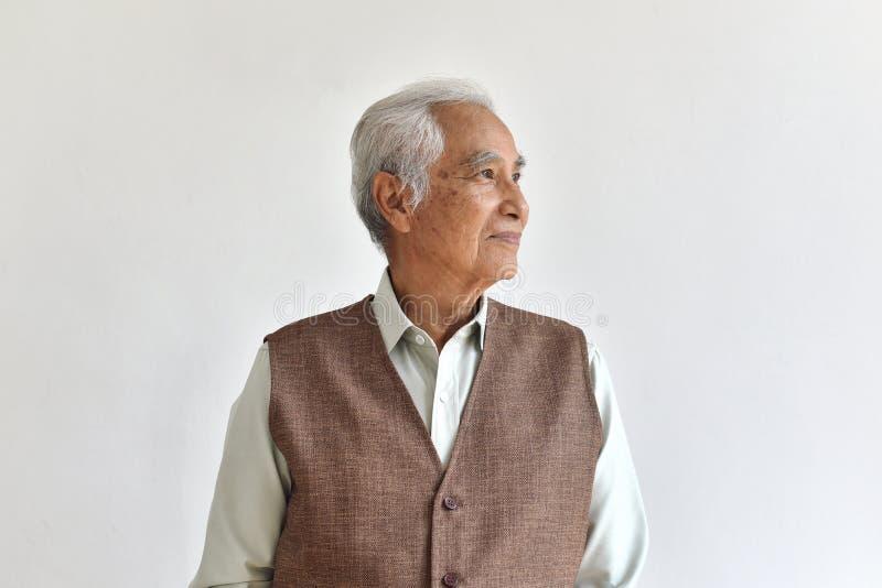 Азиатский старший старик, думая и усмехаясь престарелый на белой предпосылке стоковая фотография rf