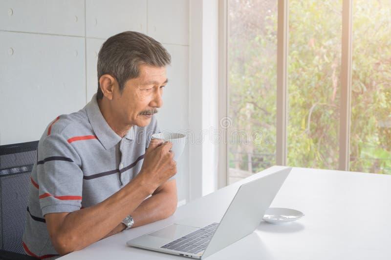Азиатский старший человек имеет белый усик В руке держа кружку кофе Сидя взгляд на к экране ноутбука на столе стоковые фото