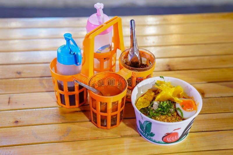 Азиатский стиль лапши в бумажном шаре с приправлять рядом с на деревянной таблице в ночи стоковое изображение rf