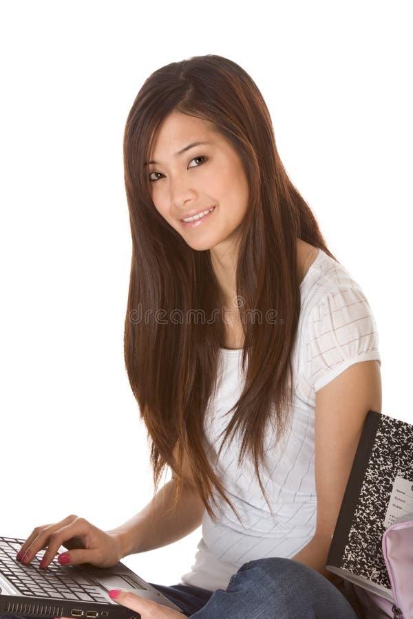 Азиатский студент в джинсыах с компьтер-книжкой стоковые фото